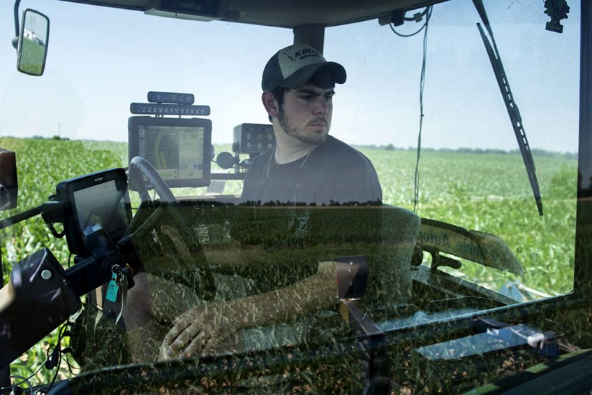 """2014-06-17 21:37:49 TO GO WITH AFP STOY by Rob LEVER, US-farm-IT-Internet-environment  Andrew Isaacson watches from the cockpit of a tractor in a corn field as screens show where he has fertilized at the Little Bohemia Creek farm on June 17, 2014 in Warwick, Maryland. The farm on Maryland's eastern shore is part of a growing """"precision agriculture"""" movement that uses high-tech tools to replace seat-of-the-pants farming. GPS auto-steered tractors cut down or eliminate overplowing and overlap that wastes fuel and time. Other technologies can sense just how much water is needed in a field to cut irrigation costs. At Little Bohemia Creek, the tractor's sensors gauge the health of various segments of a field to deliver fertilizer and other chemicals more efficiently, which has an environmental benefit. AFP PHOTO/Brendan SMIALOWSKI BRENDAN SMIALOWSKI / AFP"""