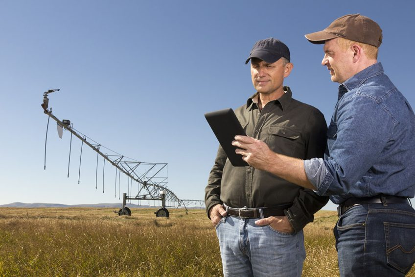 A royalty free image from the agriculture industry of two farmers standing in a field in front of irrigation equipment using a tablet PC.