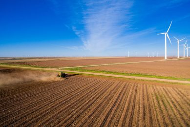A tractor is plowing up rows of barren land for future crops. The dirt is dry and dusty. Dust is kicked up by the tractor. A windmill farm is in the distance with rows of white windmills. Dry land is seen up to the horizon. The sky is bright blue with spotty clouds.