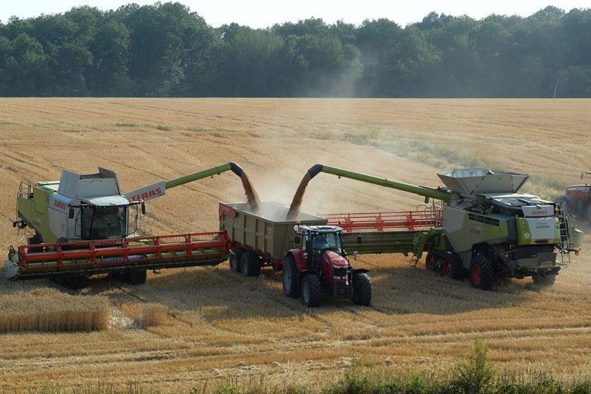 """2019-07-23 19:53:25 A French farmer and agricultural contractors harvest a wheat field, with two tracked combine harvester of 12 and 9 metres wide, in the hilly fields of """"Le Perche"""", in Combre, northwestern France, on July 23, 2019.  JEAN-FRANCOIS MONIER / AFP"""
