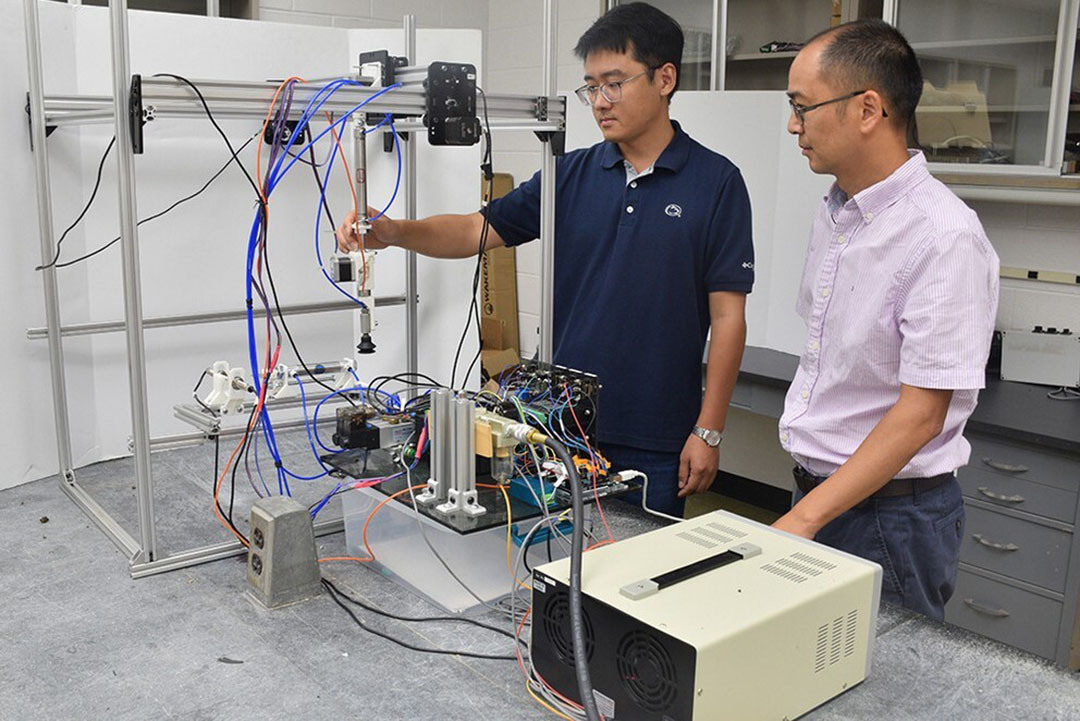 Long He (right) and visiting doctoral student Mingsen Huang testing the robotic mushroom picker in the lab. - Photo: Penn State