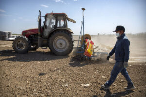 A worker walks next to a tractor during planting of a cotton field in China. - Photo: AP Photo/Mark Schiefelbein